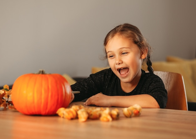 Uma menina decora uma abóbora em uma sala para o halloween. crianças decoram a casa. crianças esculpem abóbora. divertimento assustador de halloween