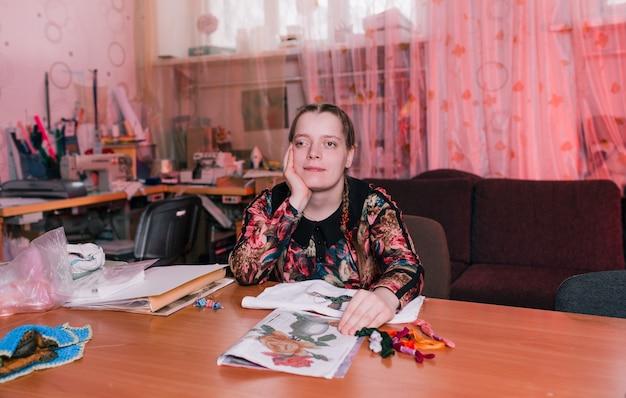 Uma menina deficiente com olhos puxados se senta a uma mesa e sorri. pessoas com deficiência.
