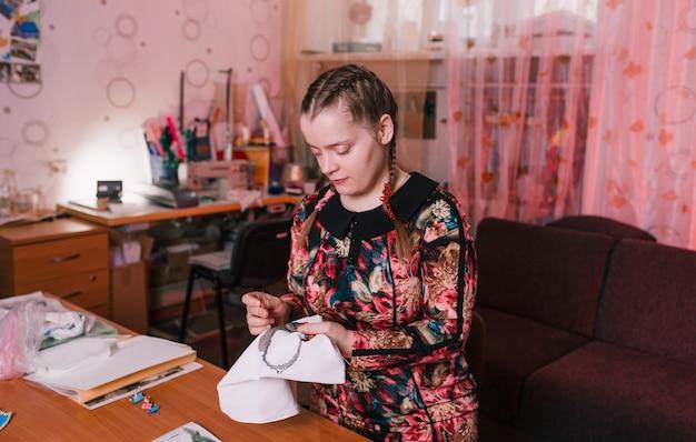 Uma menina deficiente em um vestido colorido está perto da mesa e está bordando. pessoas com deficiência.