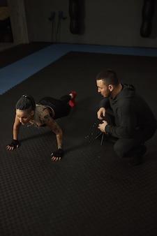 Uma menina deficiente está engajada na academia uma mulher com uma perna treina com um treinador, ela trabalha muito e não desiste diante de problemas