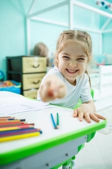 Uma menina desenha enquanto está sentada em uma mesa em uma sala contra o fundo da parede