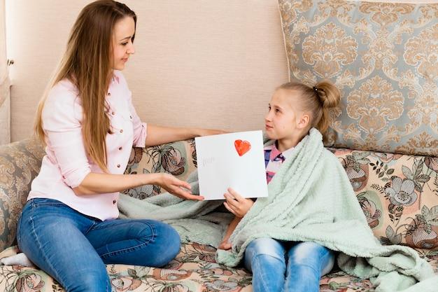 Uma menina desenha um cartão de felicitações para a mãe no dia das mães com as palavras