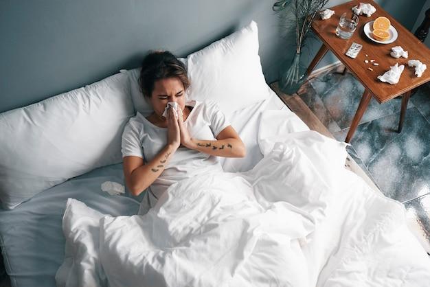 Uma menina doente assoa o nariz com lenços de papel na cama