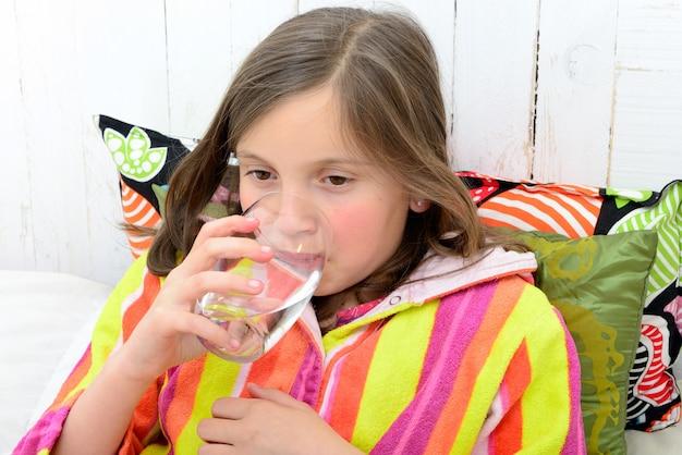 Uma menina doente, bebendo um copo de água