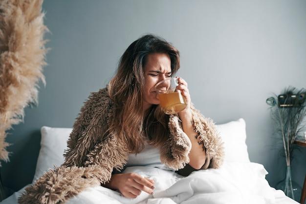 Uma menina doente com uma cara de nojo está bebendo seu remédio