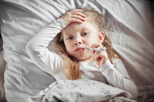 Uma menina doente deitada na cama com um termômetro
