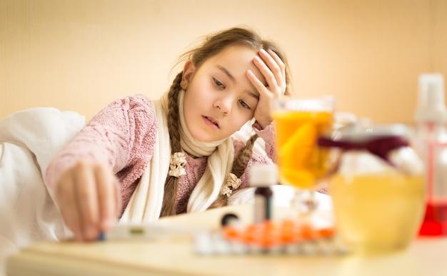 Uma menina doente deitada na cama e pegando o termômetro da mesinha de cabeceira