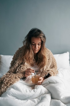 Uma menina doente na cama com um cobertor está bebendo chá quente