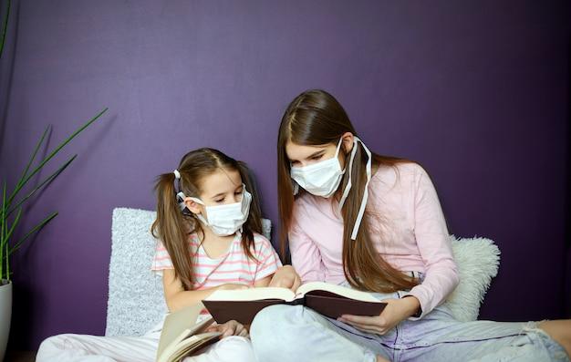 Uma menina dois na máscara médica localização no piso de madeira e lendo um livro durante a quarentena