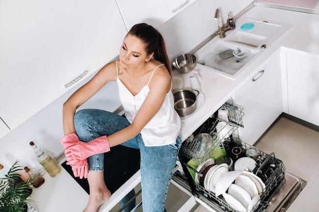 Uma menina dona de casa com luvas cor-de-rosa depois de limpar a casa senta-se cansada na cozinha. na cozinha branca, a menina lavou a louça e está descansando. muita louça lavada.