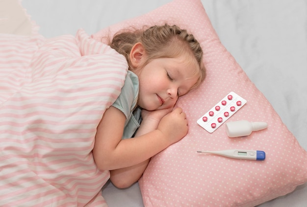 Uma menina dorme em um travesseiro e ao lado de um termômetro com medicamentos. o conceito de tratamento para a doença.