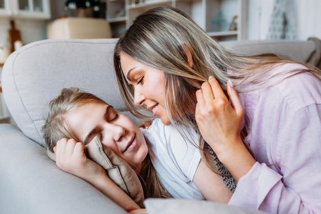 Uma menina dorme no sofá, sua mãe rouba um cobertor para sua filha, cuidado e atenção