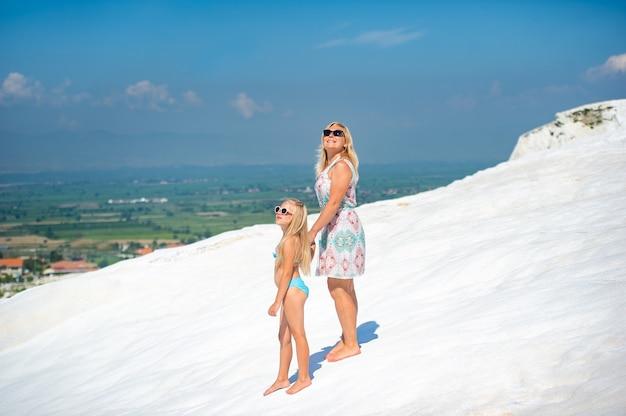 Uma menina e a mãe dela andam em uma montanha branca na cidade de pamukkale, turquia.