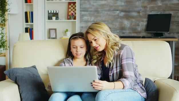 Uma menina e a mãe dela sentada no sofá da sala usando o laptop para fazer compras online.