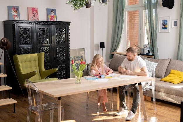 Uma menina e o pai dela sentados à mesa de madeira em uma grande sala com móveis modernos e desenhando com giz de cera colorido na quarentena doméstica