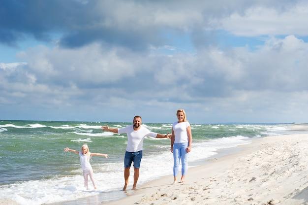 Uma menina e os pais dela caminham na praia do mar báltico, na lituânia.