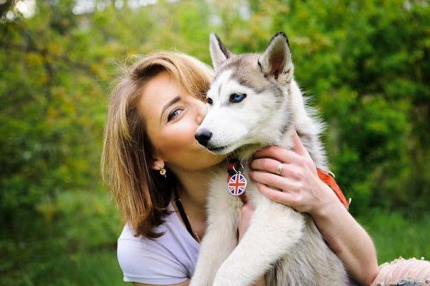 Uma menina e seu cão husky andando em um parque