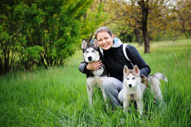Uma menina e seus cães husky andando em um parque