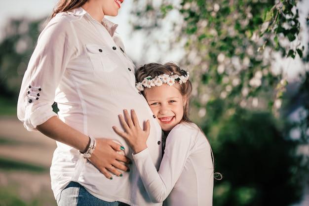 Uma menina e sua mãe grávida feliz em um passeio no parque de verão