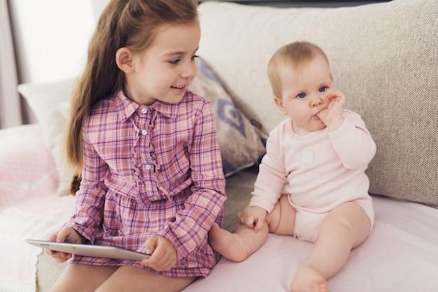 Uma menina e um bebê estão sentados no sofá