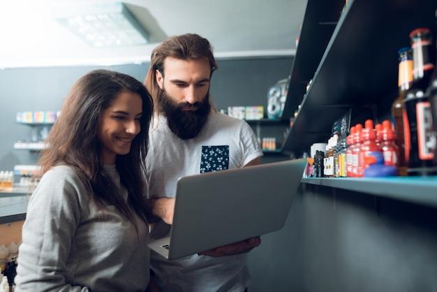 Uma menina e um homem estão em pé com um laptop.