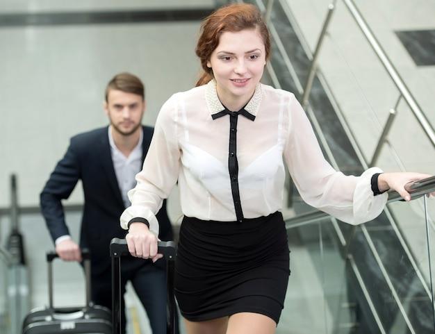 Uma menina e um homem sobem as escadas no aeroporto.