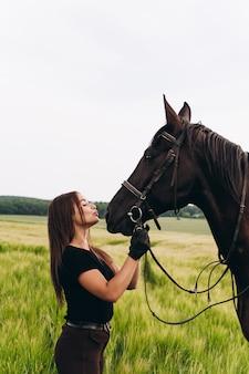 Uma menina e um jovem cavalo de esportes na natureza