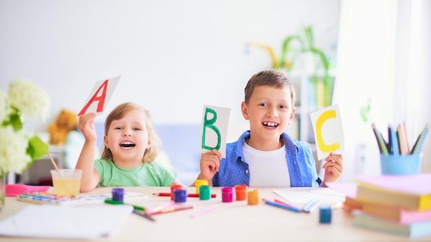 Uma menina e um menino aprendem em casa.