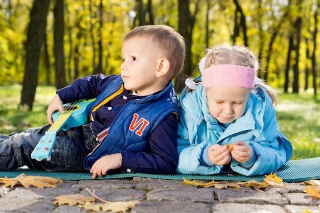 Uma menina e um menino com uma guitarra de brinquedo aproveitando o tempo livre em um parque