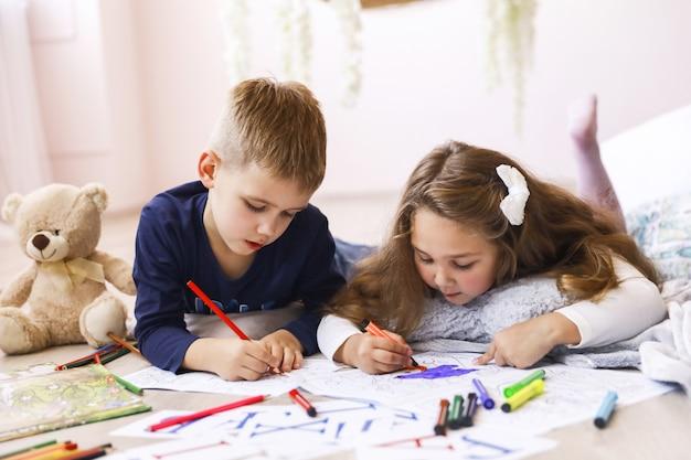 Uma menina e um menino estão desenhando livros para colorir, deitados no quarto no chão