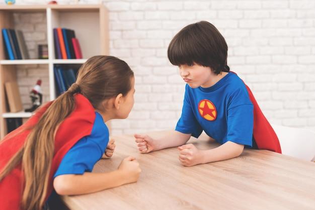 Uma menina e um menino medem sua força em uma sala iluminada.