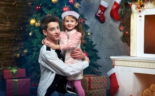 Uma menina e um menino perto da árvore junto à lareira com presentes.