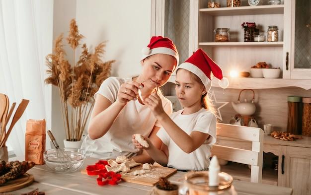 Uma menina e uma mãe com chapéus de natal estão sentadas à mesa e brincando com farinha