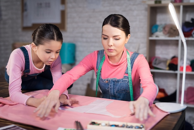 Uma menina e uma mulher adulta experimentando roupas