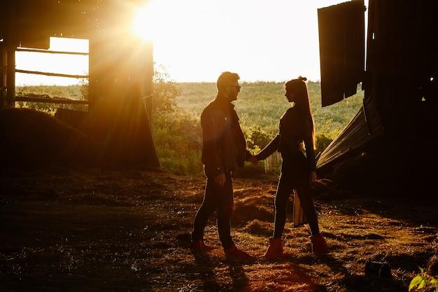 Uma menina elegante esbelta fica na frente de um cara brutal com uma barba ao pôr do sol