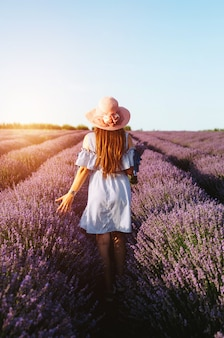 Uma menina em campos azuis da alfazema da calha do vestido azul no por do sol.