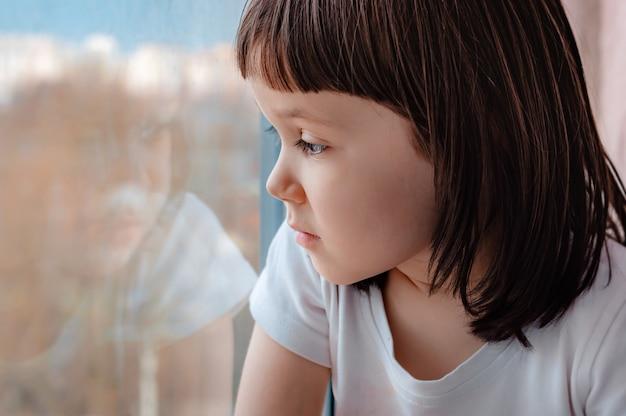 Uma menina em casa olhando esperançosamente através do vidro da janela.