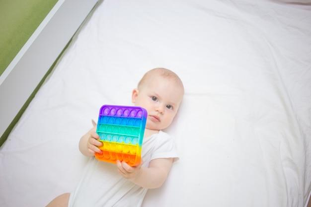 Uma menina em casa sentada na cama, jogando pop-it novo brinquedo anti-estresse, popular entre as crianças. idéia de desenvolvimento infantil.
