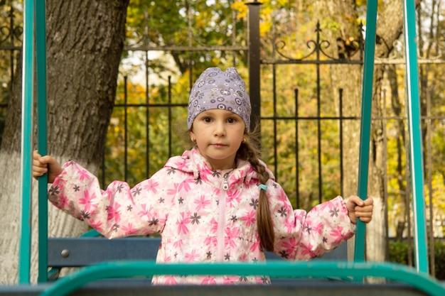 Uma menina em idade pré-escolar com uma jaqueta e um boné balança no parque no balanço.