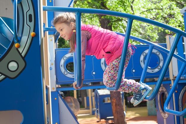 Uma menina em idade pré-escolar com uma trança sobe uma escada de ferro azul no parquinho.