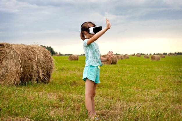 Uma menina em óculos de realidade virtual, de pé no campo e jogando.