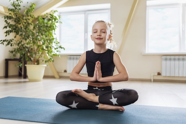 Uma menina em roupa esportiva preta praticando ioga está praticando meditação sentada em posição de lótus, mostrando com as mãos a saudação de namaste na sala