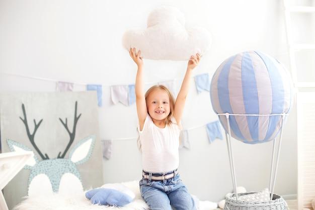 Uma menina em roupas casuais segura uma almofada de nuvens