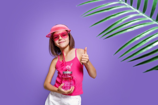 Uma menina em shorts brancos uma camiseta rosa óculos da moda rosa com uma bebida na mão e um vi ...