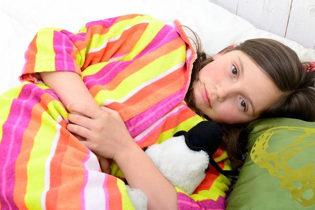 Uma menina em sua cama tem dor de estômago