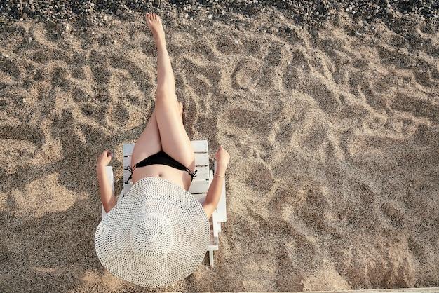 Uma menina em um chapéu que sunbathing na costa.