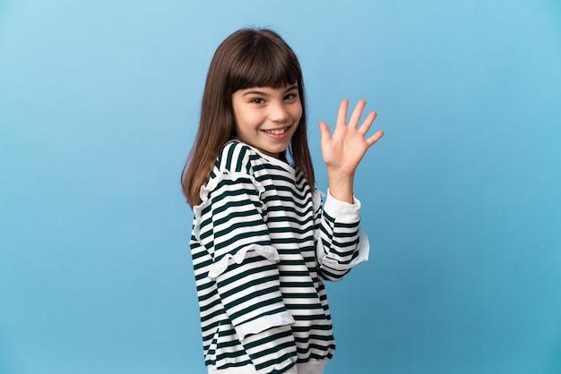 Uma menina em um fundo isolado saudando com a mão com uma expressão feliz