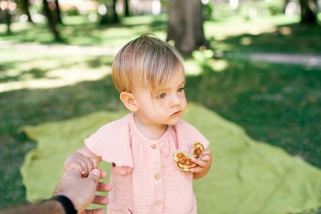 Uma menina em um gramado verde e comendo uma panqueca