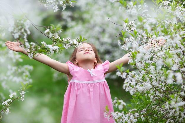 Uma menina em um jardim florescente, fecha os olhos e estica as mãos para o céu