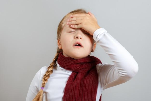 Uma menina em um lenço está sofrendo de uma doença.